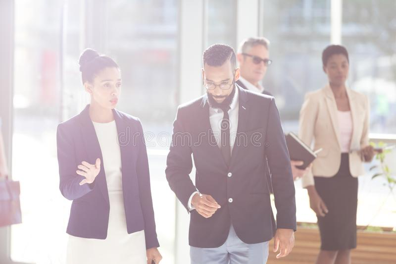 Business people interacting with each others in office lobby. Front view of mixed-race young business people interacting with each others in office lobby royalty free stock photo