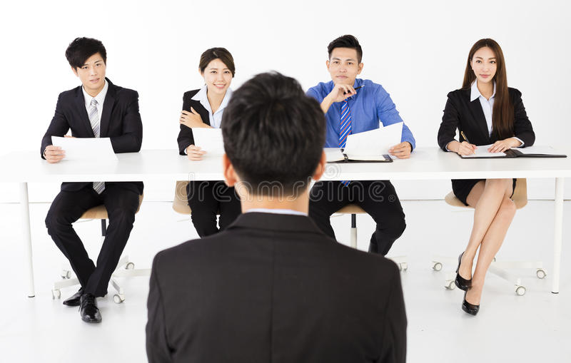 Business people interviewing young businessman in office royalty free stock image