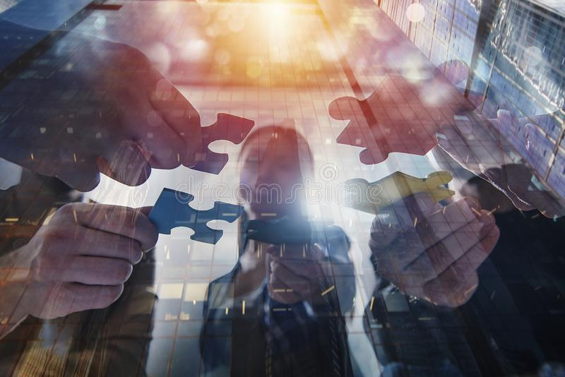 Business people join puzzle pieces. Concept of teamwork and partnership. double exposure stock photos