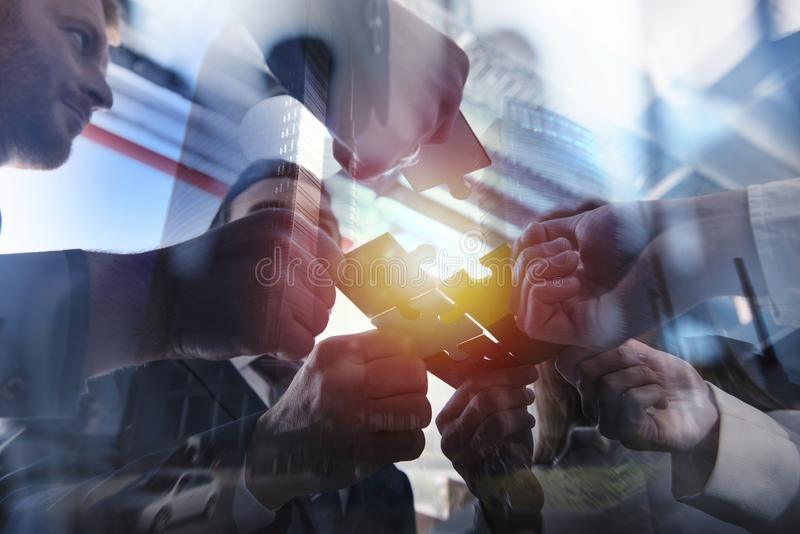 Business people join puzzle pieces in office. Concept of teamwork and partnership. double exposure with light effects. Business people join puzzle pieces in a royalty free stock photos