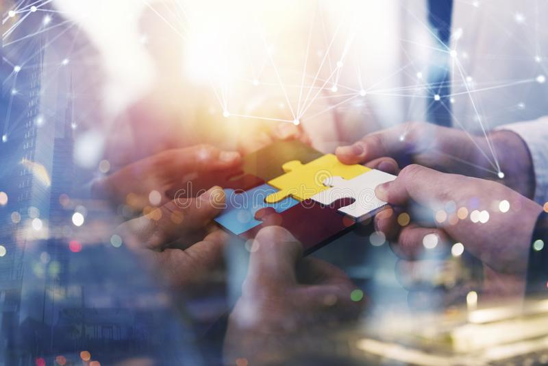 Business people join puzzle pieces in office. Concept of teamwork and partnership. double exposure with internet network. Business people join puzzle pieces in a royalty free stock image