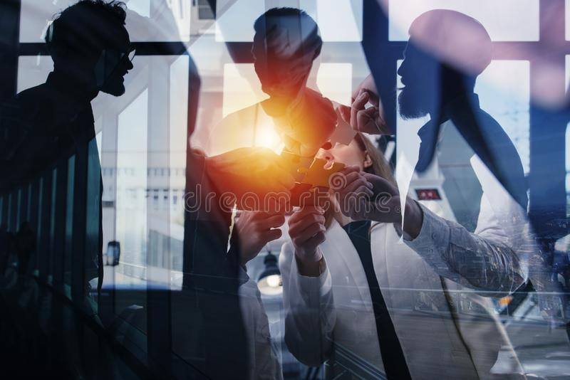Business people join puzzle pieces in office. Concept of teamwork and partnership. double exposure with light effects. Business people join puzzle pieces in a stock images