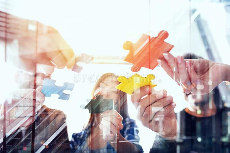 Business people join puzzle pieces in office. Concept of teamwork and partnership. double exposure with light effects. Business people join puzzle pieces in a stock photos