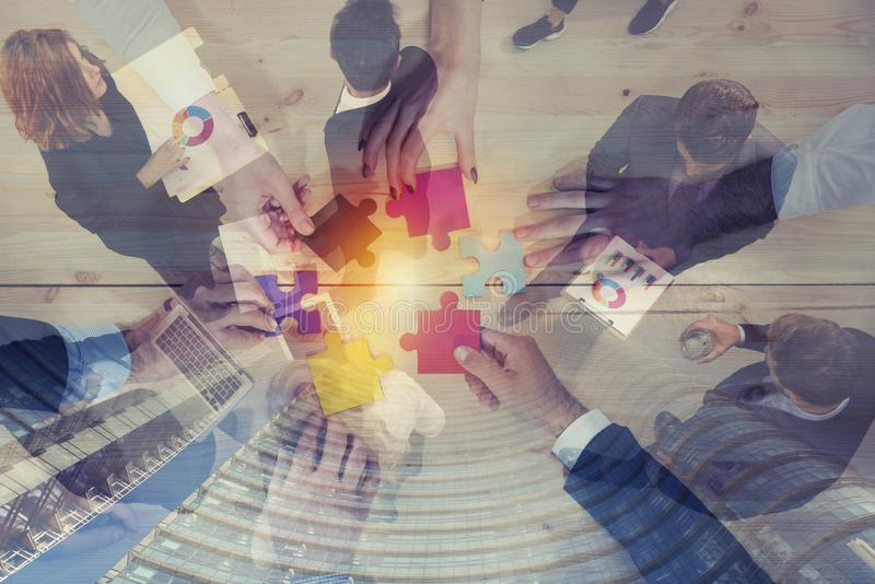Business people join puzzle pieces in office. Concept of teamwork and partnership. double exposure stock photo