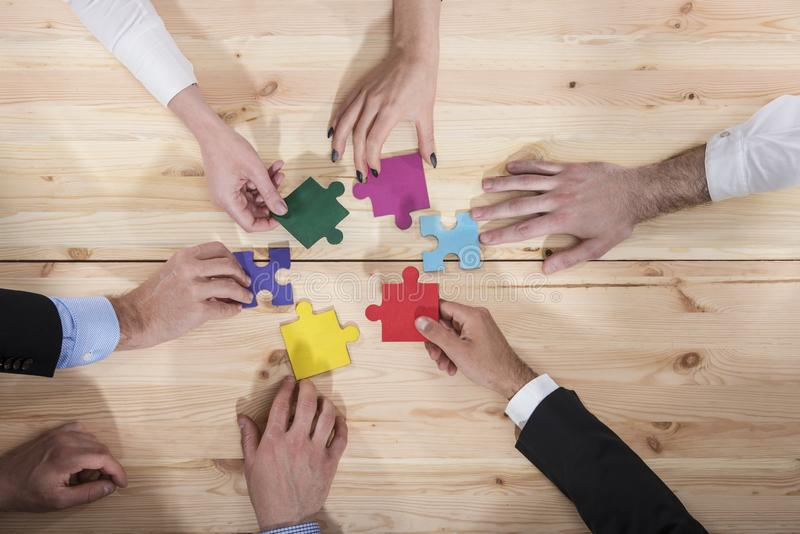 Business people join puzzle pieces in office. Concept of teamwork and partnership. Business people join puzzle pieces over a table in office. Concept of teamwork royalty free stock photo