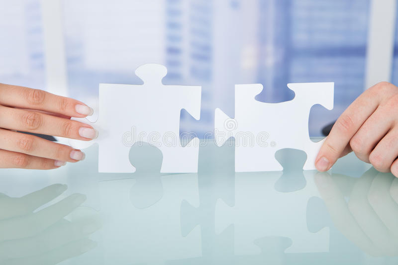 Business people joining jigsaw pieces in office stock photo
