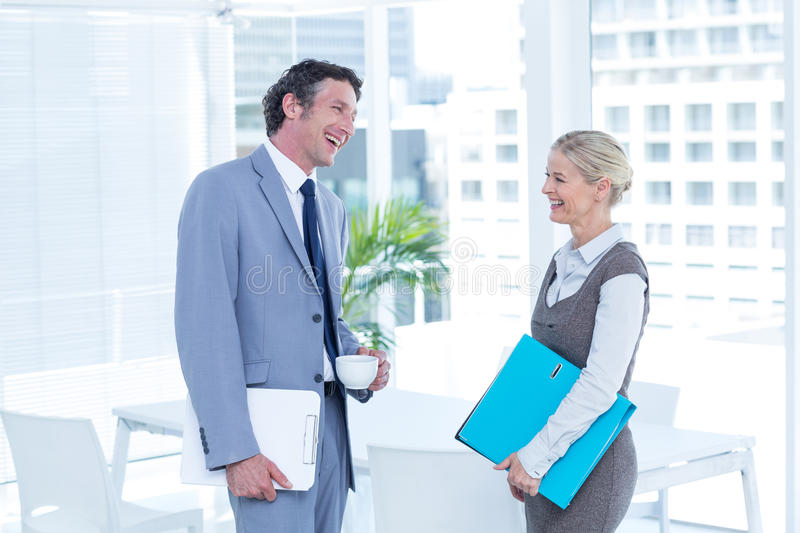 Business people laughing in an office. At work stock photos