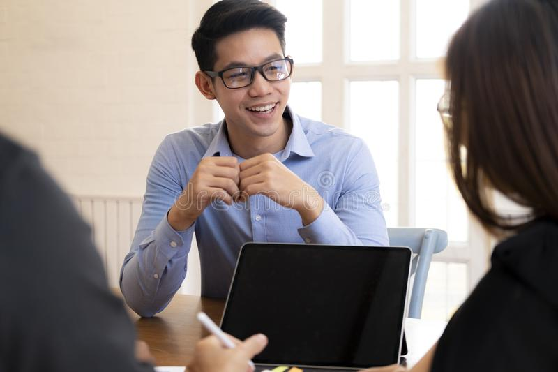 Business people laughing together while discussing paperwork during a meeting. stock image