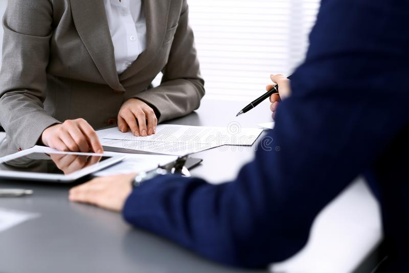 Business people and lawyer discussing contract papers sitting at the table, hands close-up. Teamwork or group operations. Concept royalty free stock photos