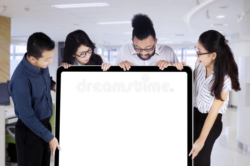 Business people looking at an empty white board with copy space stock photography