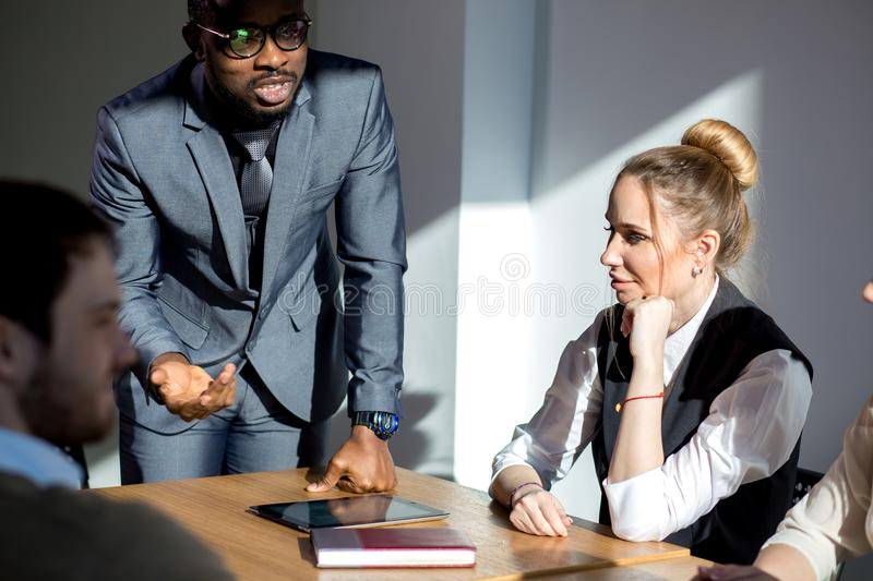 Business people listening to marketing professional african speaker presentation royalty free stock photography