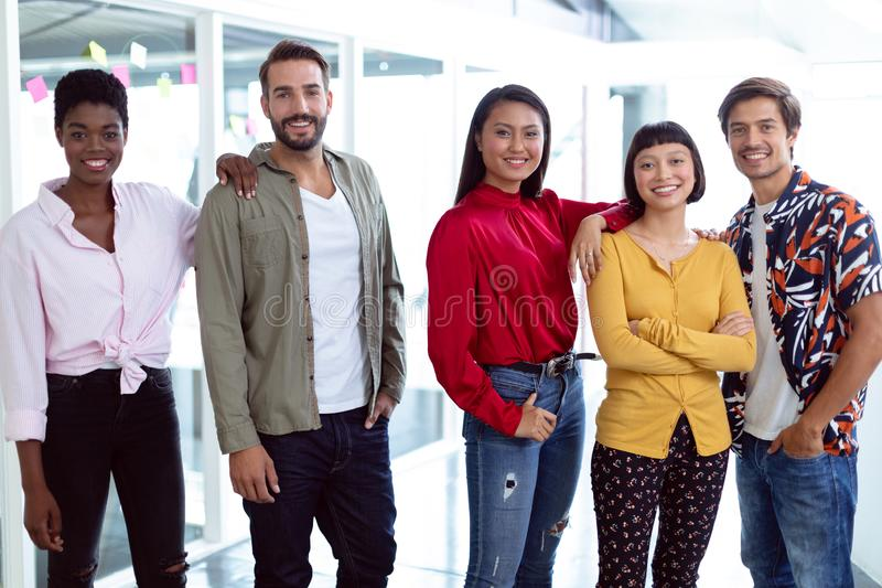 Business people looking at camera in a modern office. Front view of young diverse business people looking at camera in a modern office royalty free stock image