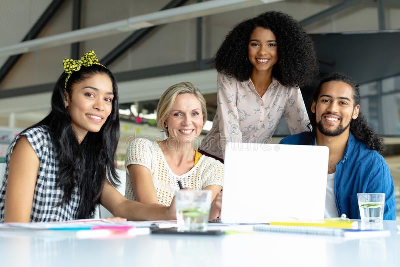 Business people looking at camera while working at conference room in a modern office. Front view of happy diverse business people looking at camera while royalty free stock image