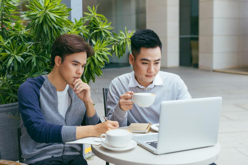 Business people looking at document and discussing while at cafe. stock images