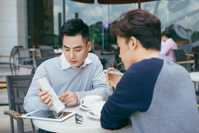 Business people looking at document and discussing while at cafe. stock image