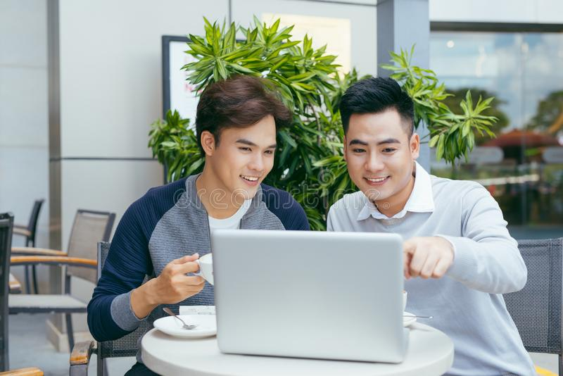 Business people looking at document and discussing while at cafe. Two businessmen working together on business report at coffee stock images