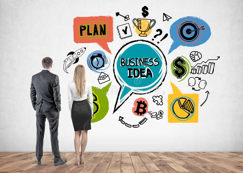 Business people looking at business idea sketch. Rear view of young businessman in glasses and blonde businesswoman looking at colorful business idea sketch stock images