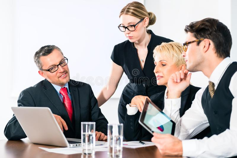 Business people looking at laptop screen royalty free stock image