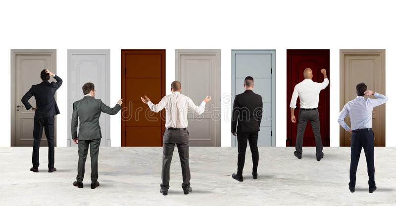 Business people looking to select the right door. Concept of confusion and competition stock photos