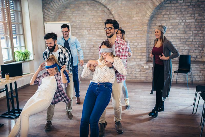 Business people making team training exercise during team building seminar, play a game of trust stock photos
