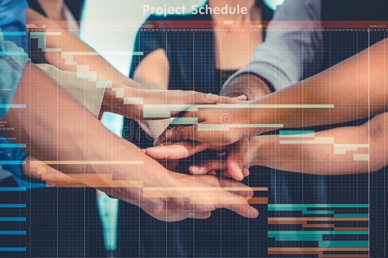 Business people male and female stacking hands together with overlay of project schedule table in meaning of teamwork and royalty free stock photo
