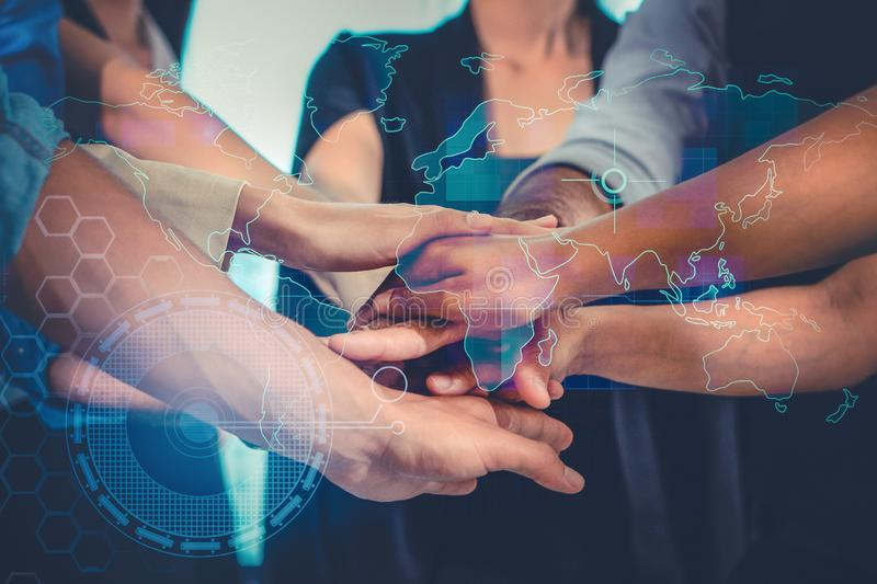 Business people male and female stacking hands together with overlay of world map and technology sign. In meaning of global technology teamwork and cooperation stock photo
