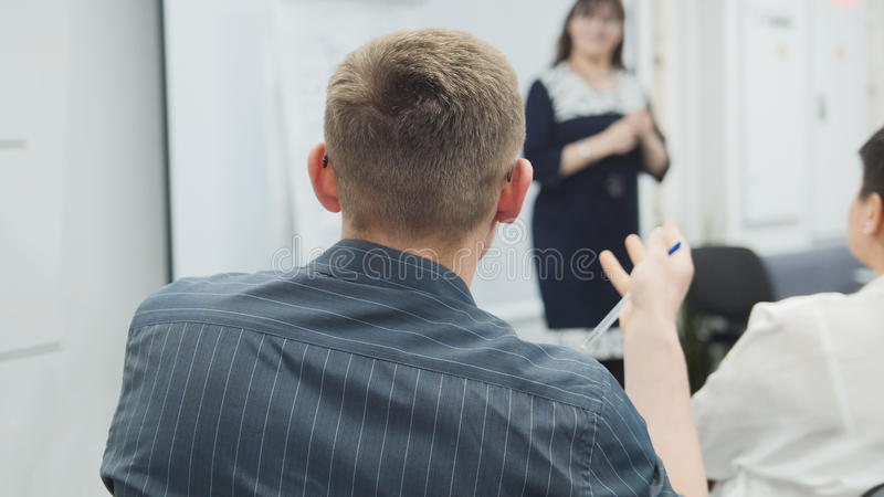 Business people - man at business seminar speaking with lecturer and audience - meeting concept stock photo