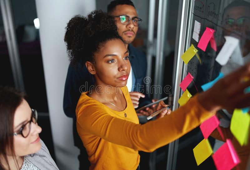 Business people in meeting brainstorming and discussing post it notes stuck on glass wall at office royalty free stock images