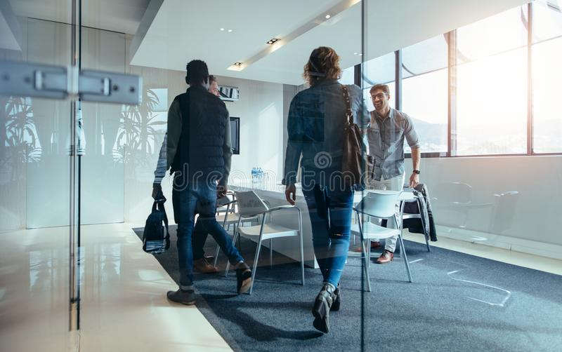 Business people meeting in conference room. Business people walking in conference room. Group of people arriving at meeting in boardroom stock photo