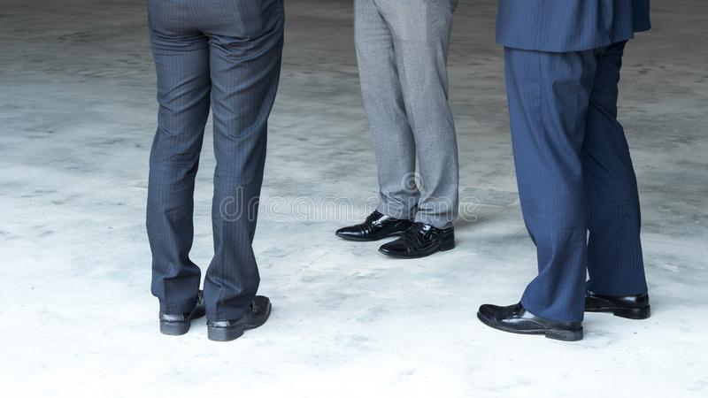 Close up leg of business men are standing meeting and consulting for discussing in the factory with flare light effect and copy sp stock photography