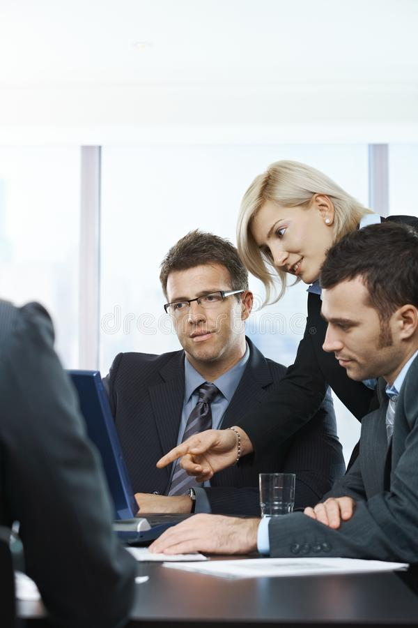 Business people at meeting. Business people looking at laptop, talking at meeting table in office royalty free stock photography