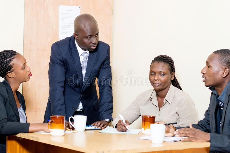 Business people meeting at the office. Business people meeting at the office discuss their plans by taking notes. They have cups of coffee and papers in front royalty free stock image