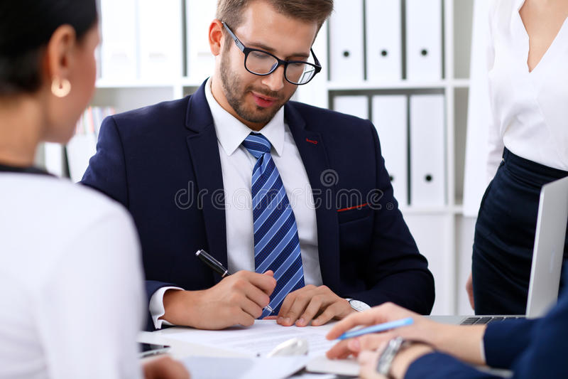 Business people at a meeting in the office. Focus on boss man while signing contract or financial papers royalty free stock photography