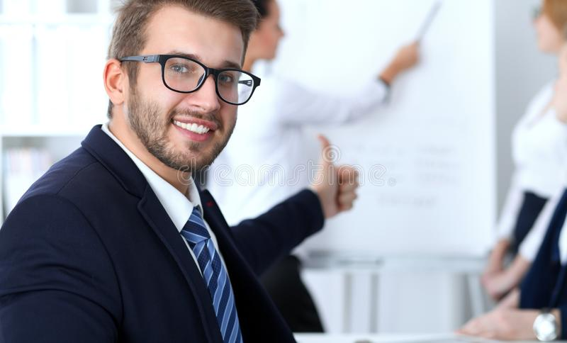 Business people at meeting in office. Focus at cheerful smiling bearded man wearing glasses. Conference, corporate royalty free stock photo
