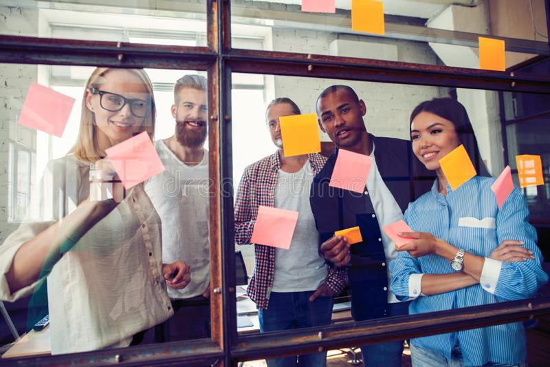 Business people meeting at office and use post it notes to share idea. Brainstorming concept. Sticky note on glass wall.  stock photos