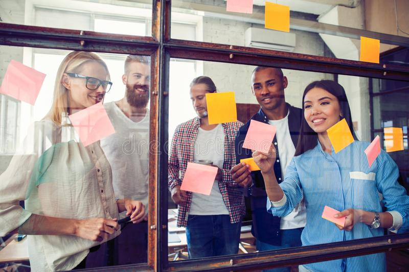 Business people meeting at office and use post it notes to share idea. Brainstorming concept. Sticky note on glass wall.  stock images
