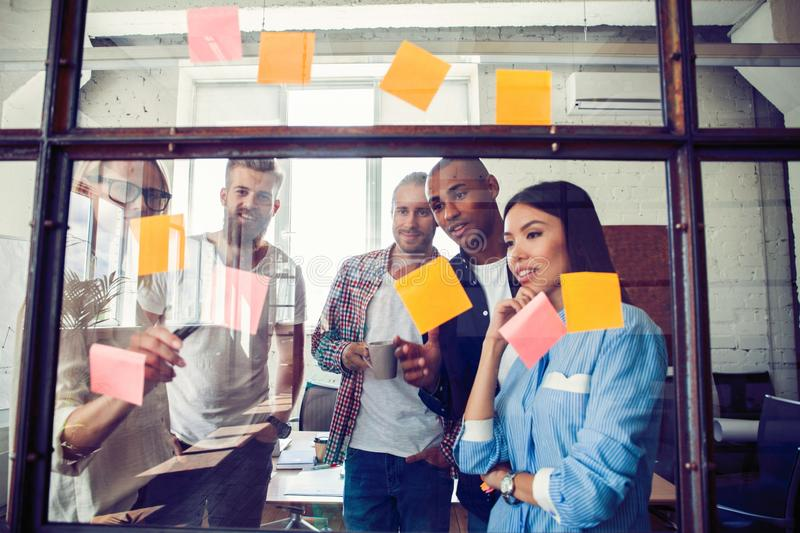 Business people meeting at office and use post it notes to share idea. Brainstorming concept. Sticky note on glass wall.  royalty free stock photo