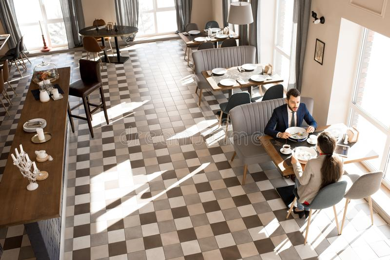 Business people meeting over lunch in modern restaurant. Directly above view of confident handsome businessman sharing his idea with business colleague while royalty free stock photos