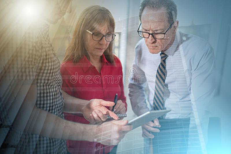 Business people in meeting working on tablet, overlayed with ray; multiple exposure royalty free stock images