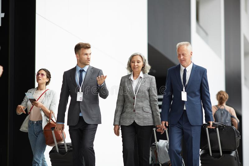 Business people moving along airport with suitcases royalty free stock image