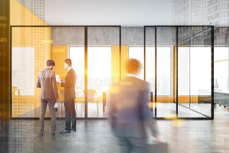 Business people near yellow office meeting room. Business people walking in modern office lobby with yellow and concrete walls, conference room and open space stock images