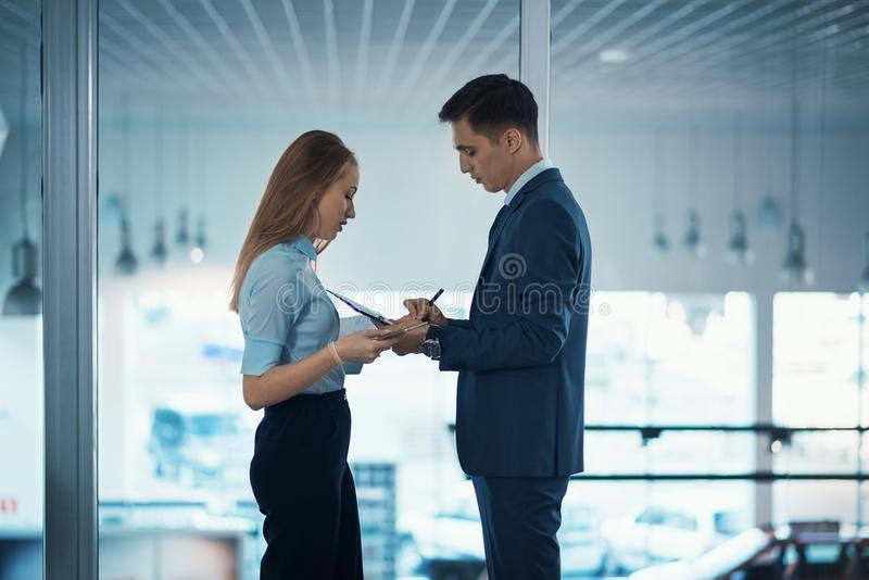 High employment. Business people in the office. Businessman in a strict suit and his assistant beautiful girl royalty free stock images