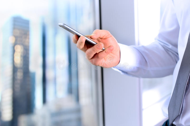 Business, people and office concept - businessman using a smartphone in the office near with window.  royalty free stock image
