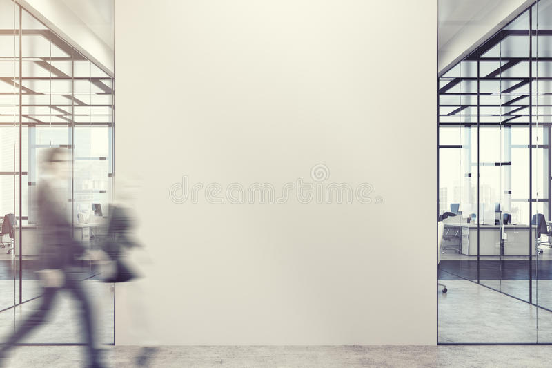 Business people in office lobby, wall. Business people in a white and glass office lobby with open space rooms and rows of computer tables. Blank wall fragment stock photos