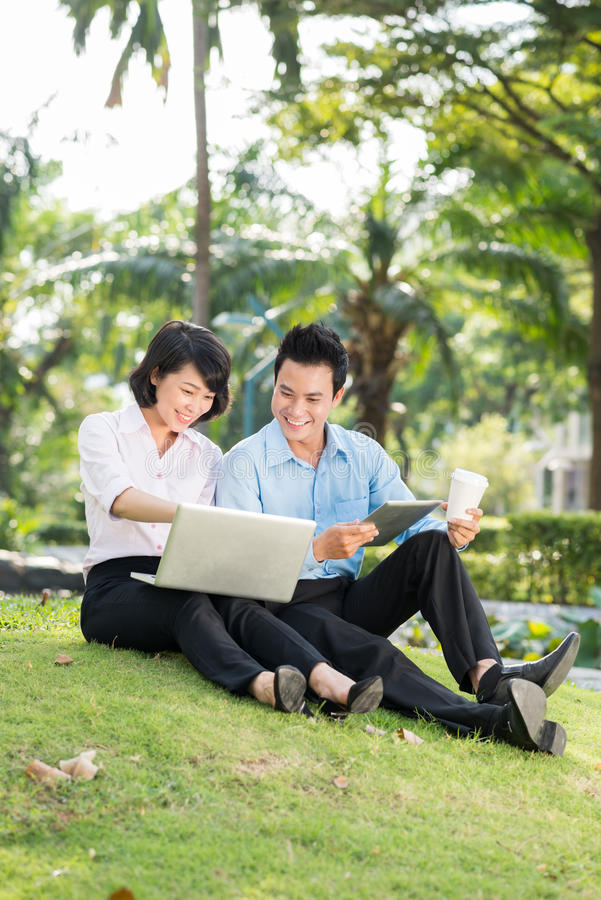 Business people in the park. Pretty Asian business lady showing her colleague something on her laptop screen stock photos