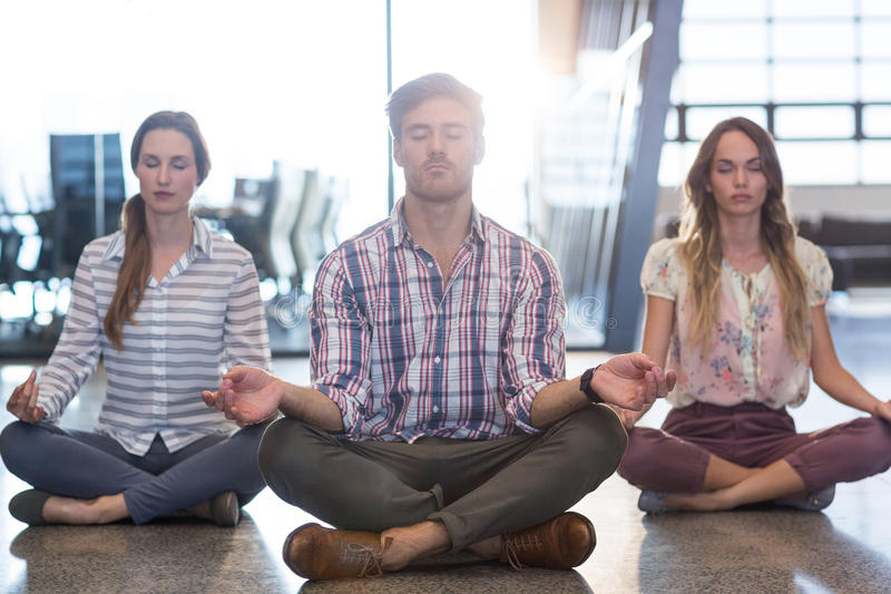 Business people performing yoga on floor royalty free stock photo