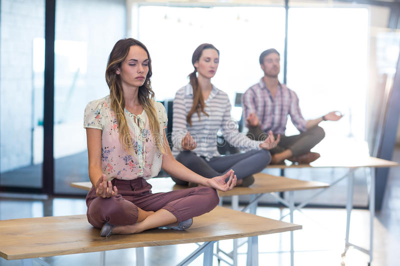 Business people performing yoga on table stock photos