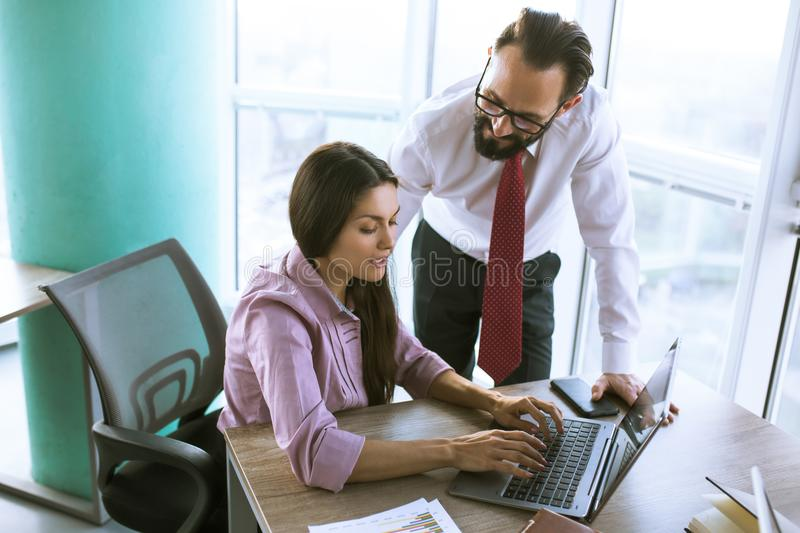 Business people planning strategy analysis. Female employee typing message on laptop. CEO standing at her desk stock photos