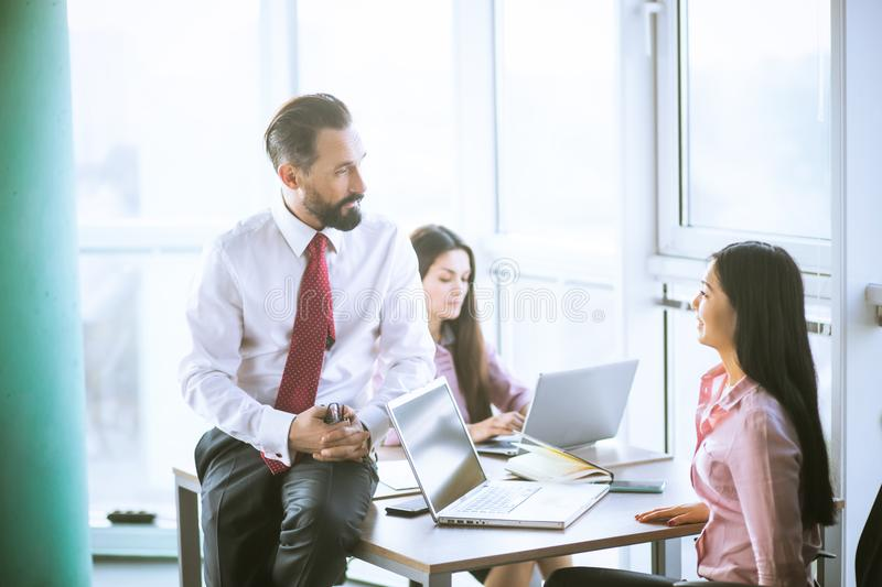 Business people planning strategy analysis. Team lead sitting on table next to manager. Office concept royalty free stock image