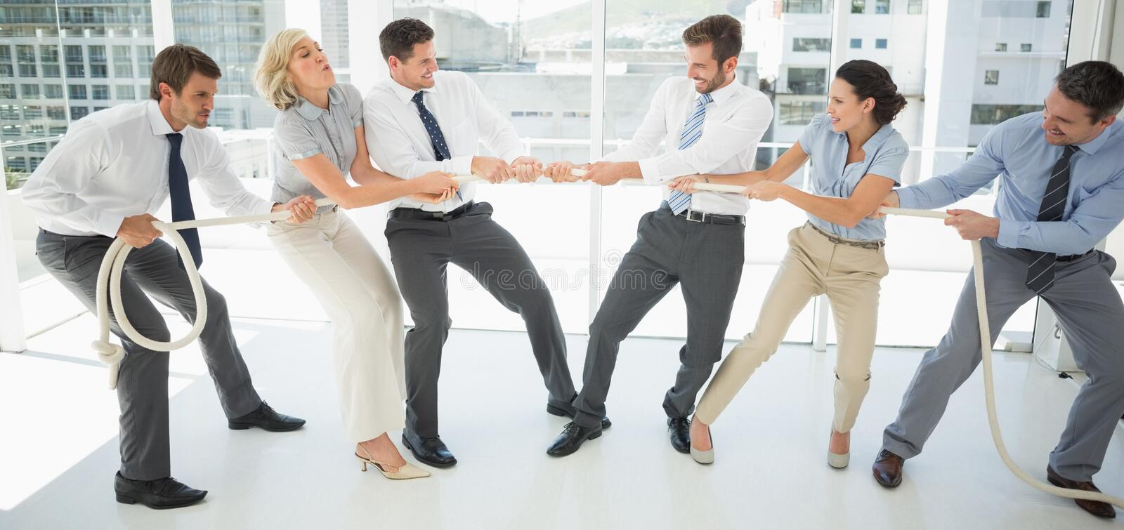 Business people playing tug of war in office royalty free stock photo